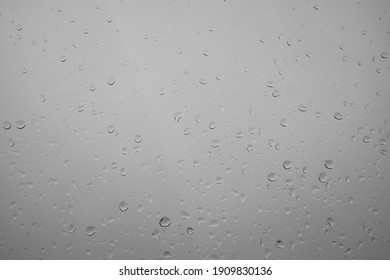 Textured water drips on white glass - background. Water belongs through a glass window. Close up of water droplets on glass. After a summer shower, heavy rain belongs on the window pane. Condensation