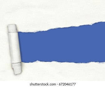 Textured white torn paper with a ripped hole showing a blue background with copy space