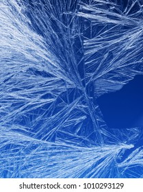 Textures and backgrounds: ice crystals on the window, frost texture over the blue sky gradient. Abstract winter pattern, seasonal background.
