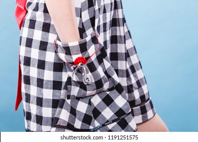 Textures and patterns concept. Woman wearing retro checked black and white dress holding her hands in pocket studio shot on blue background