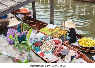 Tha Kha Floating Market, Samut Songkhram, Thailand - July 30, 2017 : The atmosphere of trading goods and food, Unidentified tourists and merchants on vintage boats at Tha Kha Floating Market.