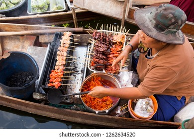 Tha Kha, Thailand - December, 12th, 2018: Woman cooking pork in her traditional thai boat in Tha Kha floating Market.