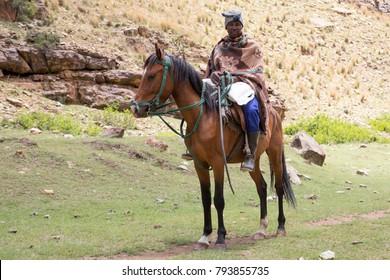 Thaba Tsheka, Lesotho, 12/23/2017 Basotho rider on his horse, wearing the traditional blanket.
