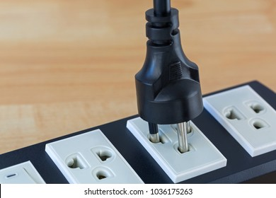 Thai 2 round power pins plug with earth pin plugging in compatible extension cord, with blurred wooden background for copyspace
