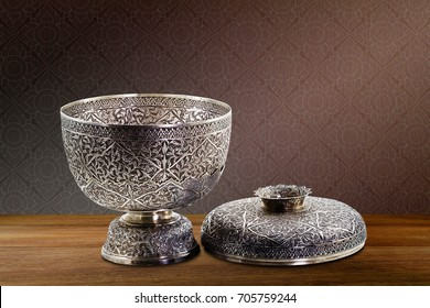 Thai antique ancient grunge silver bowl on wooden tabletop on vintage brown purple concrete wall background, still life