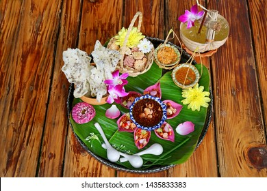 Thai Appetizer Set of Fresh Lotus Petal Wrapped and Crispy Fried Rice Cakes with Calamansi Citrus Juice Served on Wooden Table