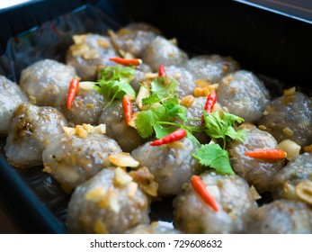 Thai appetizer, Steamed tapioca balls with peanut and pork filling with chilis, coriander and garlic in a black plastic food tray box for take away home.