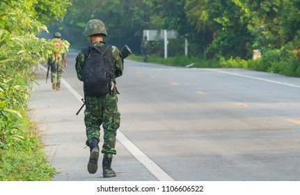 Thai army soldier holding gun and carry bag patrolling in southern Thailand.