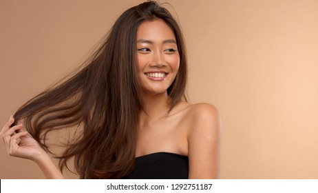 thai asian model watching aside smiling wide andtouching her hair