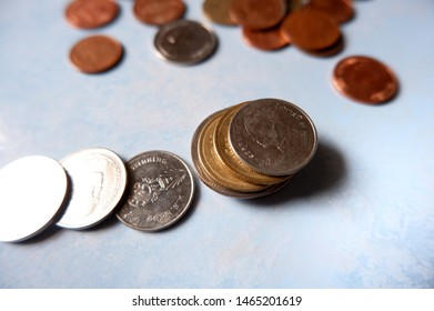 Thai baht coins are stacked together, with many scattered behind, Supporting the Thai baht appreciation in the region.