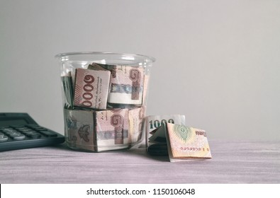 Thai Baht money inside bottle with banknote and calculator on white wood table