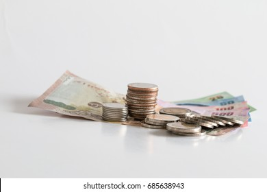 Thai baht money, various colorful banknotes and multi level stacks of coins on white background, indicating step up economy or financial growth concept