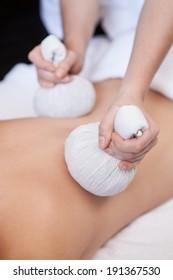 Thai Ball Massage. Woman in day SPA getting thai herbal compress massage.