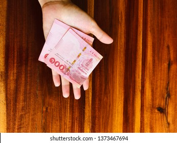 Thai banknote on hand and wood background.Red Thai Banknote on hand and brown backdrop.200 bath thai banknote.