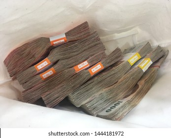 """Thai banknotes in bag,One hundred baht,One thousand baht.With tag and text in Thai .The Thai word means """"kind of one hundred Baht"""""""