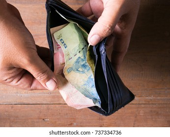 Thai bath bill one hundred, fifty and twenty in back wallet with hands open. On the near end of the month money in the pouch is very low.