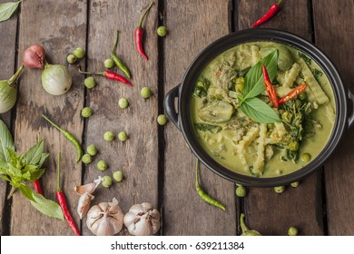 Thai beef green curry with ingredients on old wooden background
