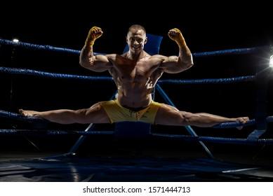 Thai boxer on boxing ring, stretch out, full split, horizontal photo