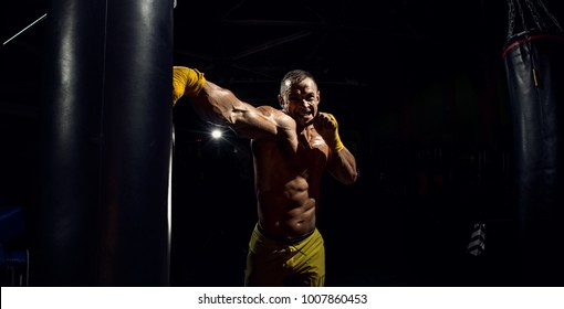 Thai boxer punch kick by punching bag, black bacground, horizontal photo