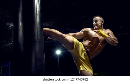 Thai boxer punch kick by punching bag, black background, horizontal photo