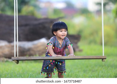 Thai boy 2 years old 5 months dressed in folk costume Playing with the seat swings.