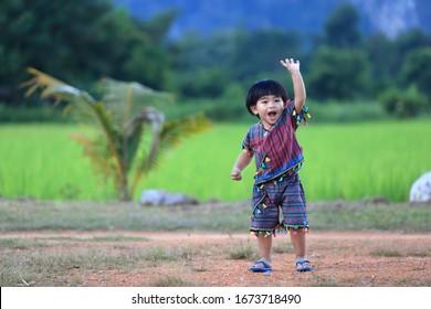 Thai boy 2 years old 5 months dressed in folk costume Wear slippers Showing happy gestures.