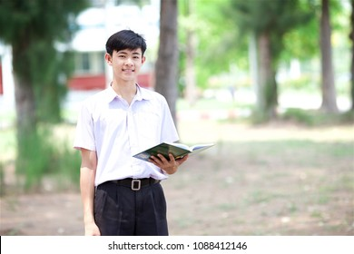 Thai boy in Thai student uniform (black shorts) with nature background, also holding book in his hand