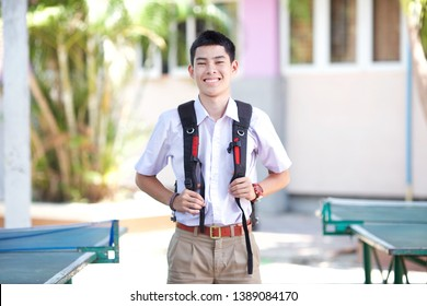 Thai boy in Thai student uniform (brown/khaki shorts), holding a backpack, and standing among table tennis tables