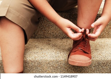 Thai boy is tying the laces student shoe