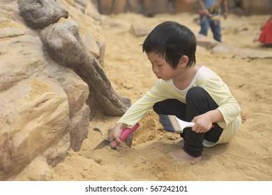 Thai boy using brush and shovel finding hidden artifact under the ground