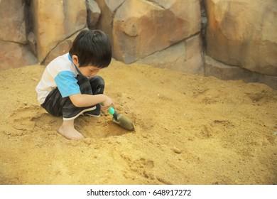 Thai boy using hand shovel digging sand to find hidden asset