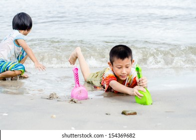 Thai brother and sister ages 6 and 4 have fun digging in the sand at the beach