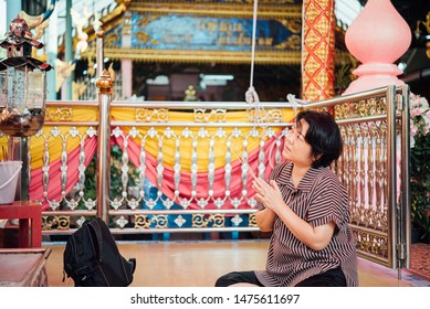 Thai buddhism people in buddhist pray for benefaction worship by incense and garland to Buddha or spirit-house at shrine or Thai temple (Wat Thai)