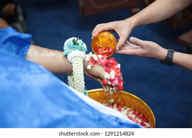 Thai Buddhist funerals bathing ceremony, ceremonial pouring of water shortly after death. Guests, one by one, pour water infused with  holy water over the hand of the deceased.