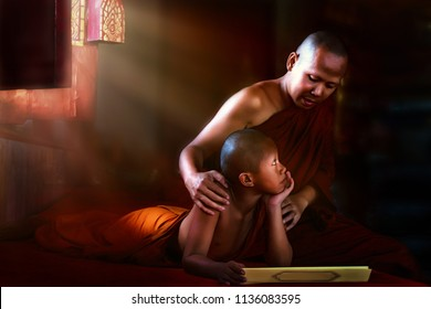 Thai Buddhist monk teaching Buddhist novice Buddhism lessons from Buddist scripture in dark temple with light ray shining from window