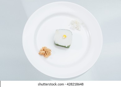 """Thai Candy """"TACO"""" preparation on white bowl with coconut and dried shredded pork,"""