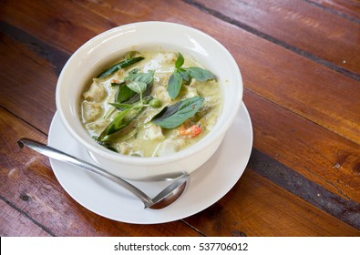 Thai chicken green curry with old wooden background.closeup green curry with chicken (Kang Keaw Wan Gai) isolated on white background, Thai local food.
