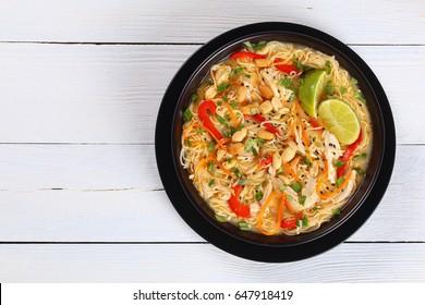 Soupe de nouilles au curry vert de poulet au lait de coco, légumes et herbes dans un bol noir arrosé de graines de sésame et de cacahuètes sur plan de travail en bois, recette authentique, vue d'en haut