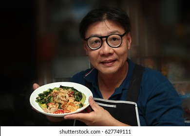Thai Chinese food ,Chef holding a plate of fried big noodle with marinated chicken in soy sauce and vegetable call Sen Yai Pad Cee Oue in Thai.