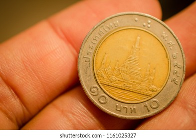 Thai coin on hand,ten baht.concept for value of the baht.