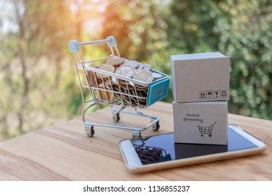 Thai coins in trolley and stack of cardboard box on smartphone with nature background. Consumers can buy products anywhere directly from seller over internet. Online shopping and e-commerce concept.