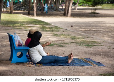 Thai couple lover people sit and dating on mat and stone bench on Samila Beach at Hat Yai city in Songkhla, Thailand