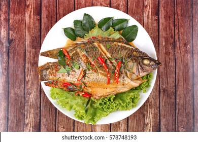 Thai cuisine, Curry-fried Tilapia fish with spicy topping on white dish.