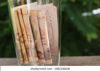 Thai Currency 1000 Baht, Thai money banknote one thousand accumulated in the glass on the wooden floor, Concept Savings