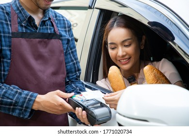 Thai customer using credit card for contactless payment after buy baked bread. Asian people payment with thru drive on the car.