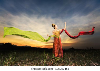 Thai dancing girl with northern style dress in rice field in front off background of sunset