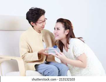 Thai daughter giving gift to mother isolated