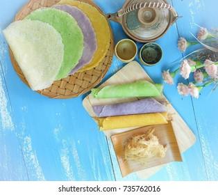 Thai dessert is called Roti Sai Yai, many colors are laid on blue wooden floor.