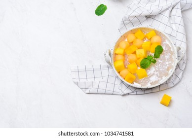 Thai dessert food style : Top view of homemade sago with coconut milk and topping with mango cut into squares and cantaloupe ball in a white bowl  and placed on a marble table with a tablecloth plaid.