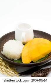 Thai dessert of mango with sticky rice served on palm wooden dish